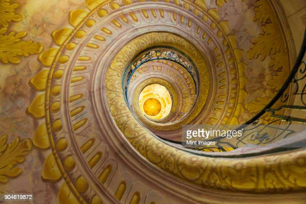 Low angle view of spiral staircase decorated with murals of golden Acanthus flowers and ornamental borders.