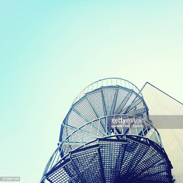 low angle view of spiral stairs against clear sky - spiralmuster stock-fotos und bilder