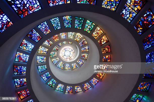 Low angle view of spiraling stained glass windows in church