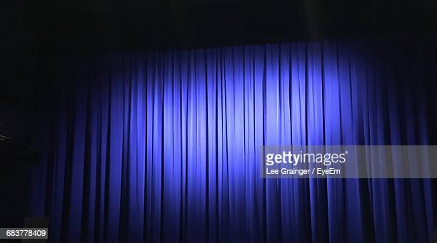 Low Angle View Of Spot Lit On Closed Purple Curtains At Theater