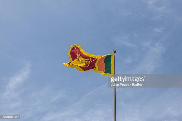 low angle view of sri lankan flag against cloudy sky - sri lankan flag stock pictures, royalty-free photos & images