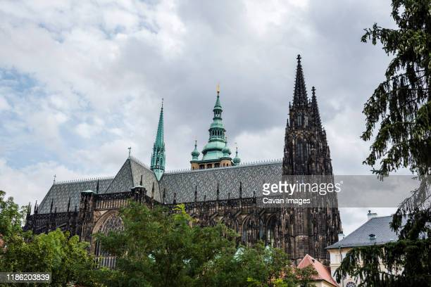 low angle view of st vitus cathedral against cloudy sky - st vitus's cathedral stock pictures, royalty-free photos & images