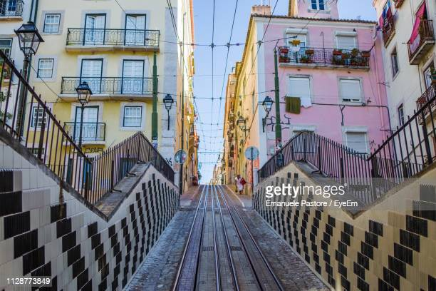 low angle view of staircase amidst buildings in city - provincie lissabon stockfoto's en -beelden