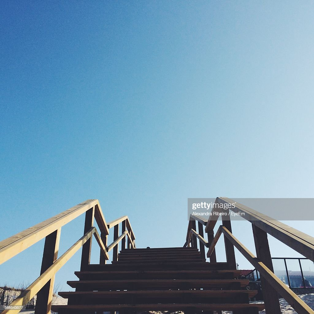 Low Angle View Of Staircase At Beach Against Clear Blue Sky : Stock Photo