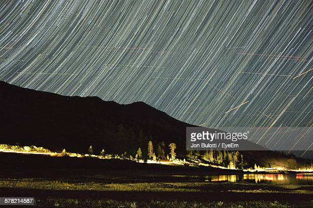 Low Angle View Of Star Trails Over Mountain At Night