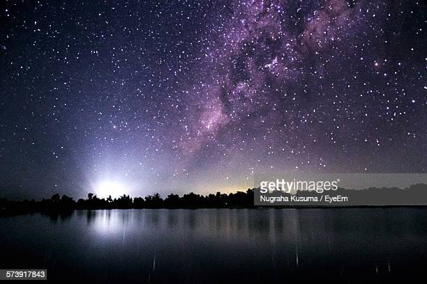 low angle view of starry sky over river - costellazione foto e immagini stock