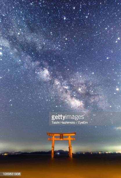 Low Angle View Of Stars Over Torii Gate And River Against Sky At Night