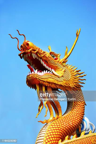 low angle view of statue against blue sky - chinese dragon stock pictures, royalty-free photos & images