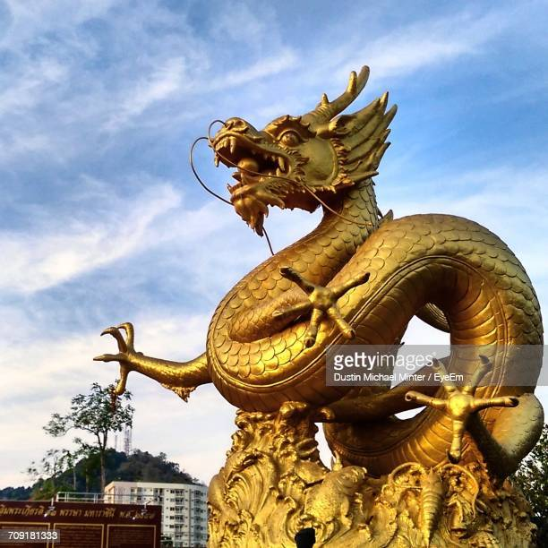 low angle view of statue against cloudy sky - chinese dragon stock photos and pictures