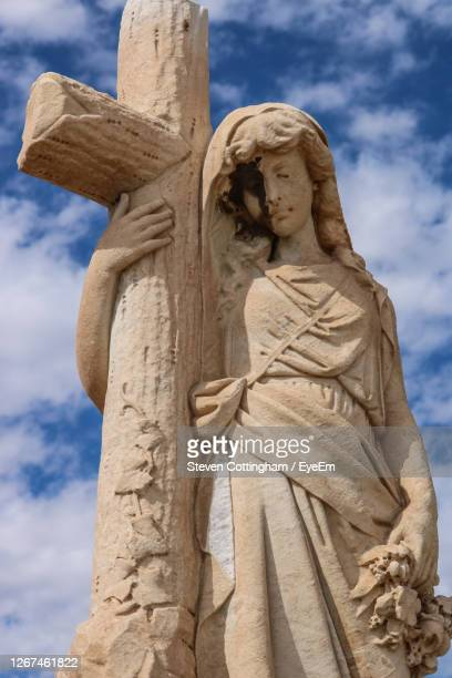 low angle view of statue against sky in cemetery - steven cottingham stock-fotos und bilder