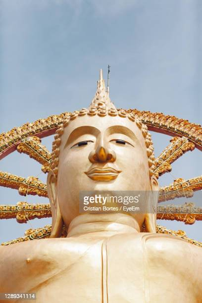 low angle view of statue against temple against sky - bortes stock-fotos und bilder