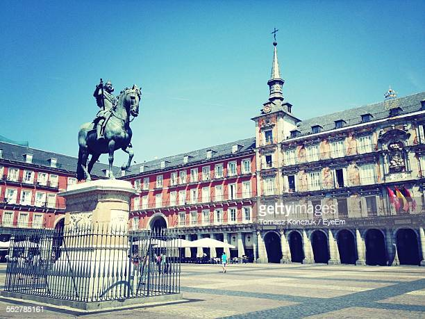 Low Angle View Of Statue Amidst Plaza Mayor Against Clear Blue Sky