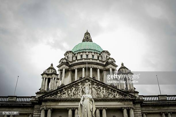 Low Angle View Of Statue And Belfast City Hall Against Cloudy Sky