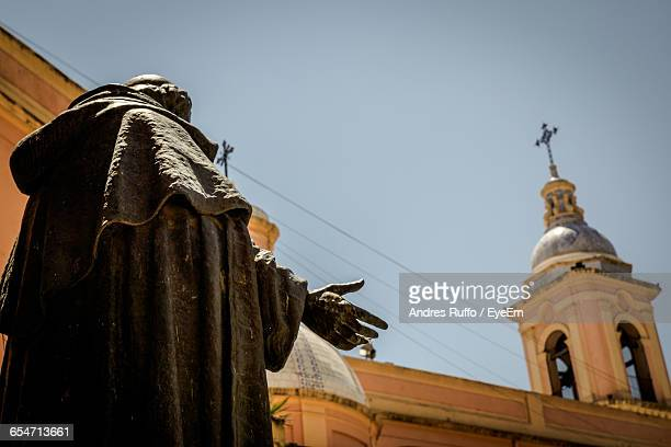 Low Angle View Of Statue And Church Against Clear Sky
