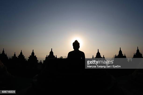 low angle view of statue at temple against sky during sunset - yogyakarta stock pictures, royalty-free photos & images