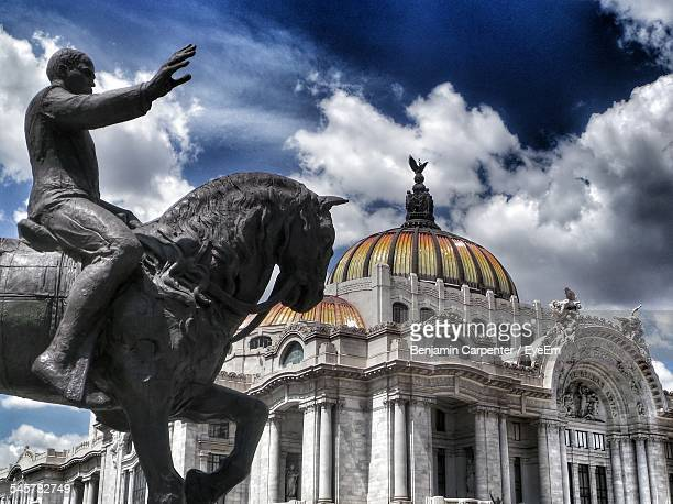 Low Angle View Of Statue By Palacio De Bellas Artes Against Cloudy Sky
