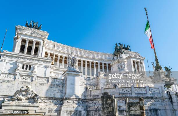 low angle view of statue of building against blue sky - altare della patria stock pictures, royalty-free photos & images