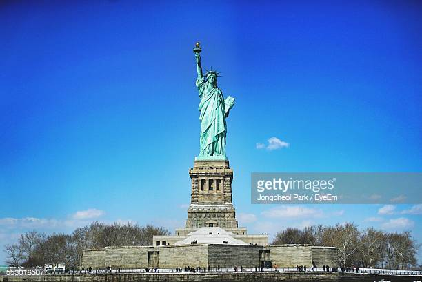 Low Angle View Of Statue Of Liberty Against Blue Sky
