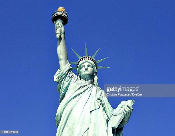 Low Angle View Of Statue Of Liberty Against Clear Blue Sky