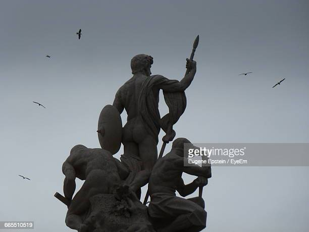 low angle view of statues against sky - epstein statue stock pictures, royalty-free photos & images
