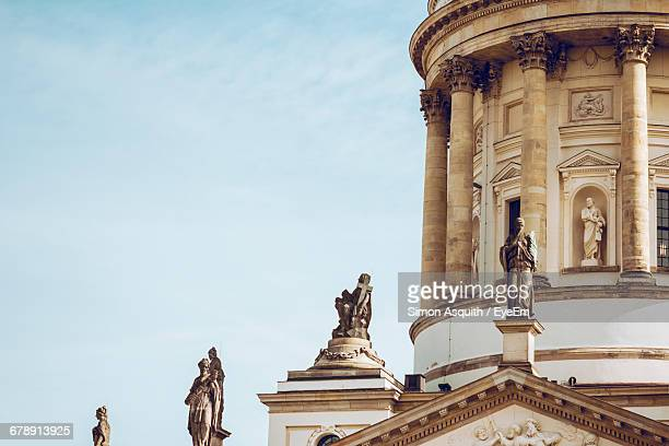 low angle view of statues at neue kirche against sky in city - gendarmenmarkt stock pictures, royalty-free photos & images
