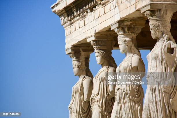 low angle view of statues at old ruins against clear sky - athen griechenland fotos stock-fotos und bilder