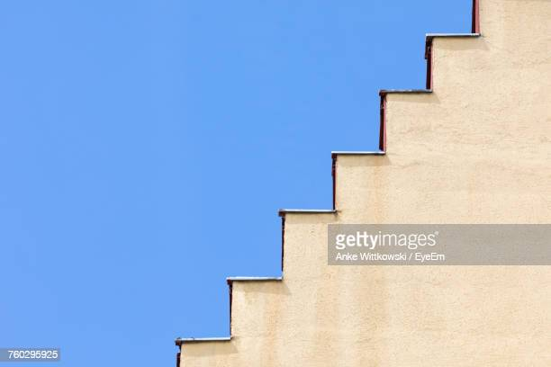 low angle view of steps against clear blue sky during sunny day - steps stock photos and pictures