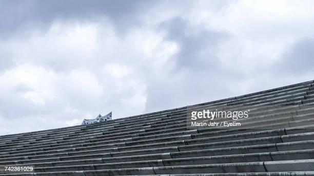 low angle view of steps against cloudy sky - elbphilharmonie stock pictures, royalty-free photos & images