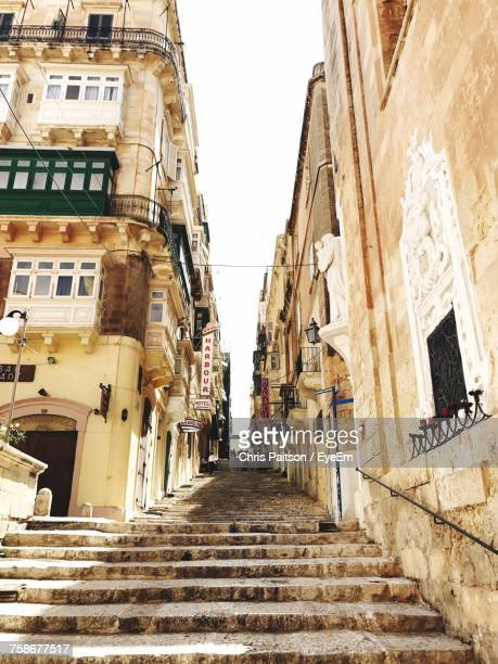 low angle view of steps amidst buildings against sky - maltese islands stock photos and pictures