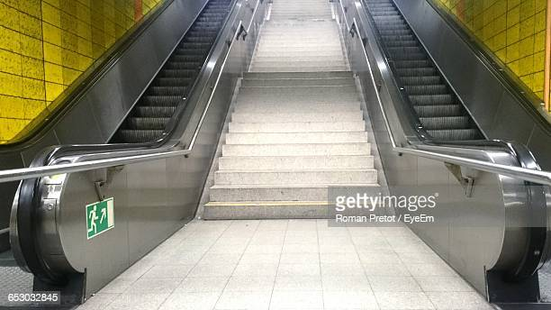 low angle view of steps amidst escalators in subway - roman pretot stock-fotos und bilder