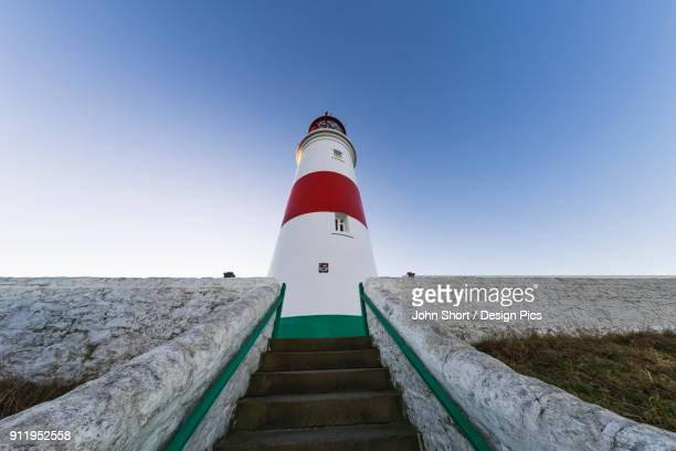 Low Angle View Of Steps Leading To A Lighthouse Against A Blue Sky