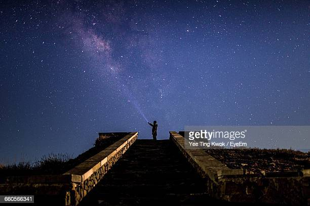 Low Angle View Of Steps Leading Towards Man Against Star Field At Night