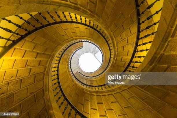 low angle view of stone spiral staircase towards skylight. - santiago de compostela stock pictures, royalty-free photos & images