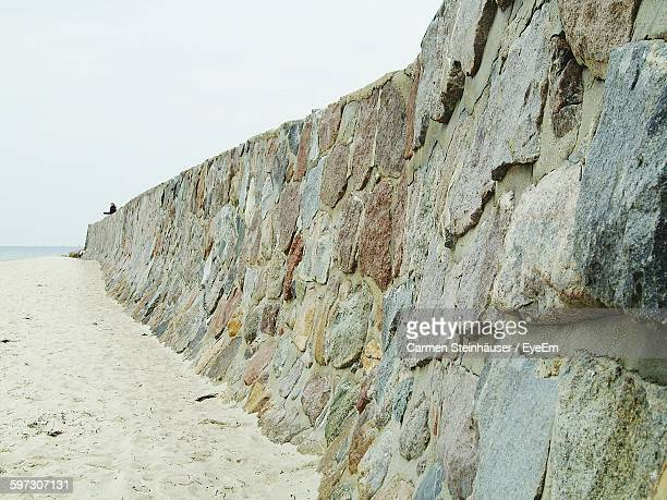 Low Angle View Of Stone Wall On Beach Against Clear Sky