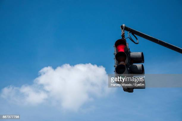 Low Angle View Of Stop Light Against Blue Sky