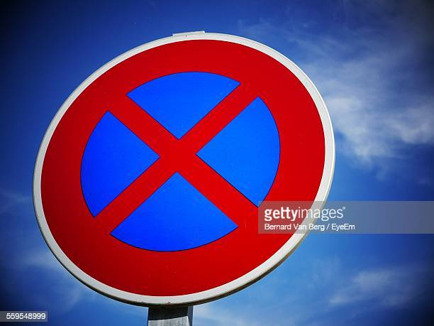 Low Angle View Of Stop Sign Against Blue Sky