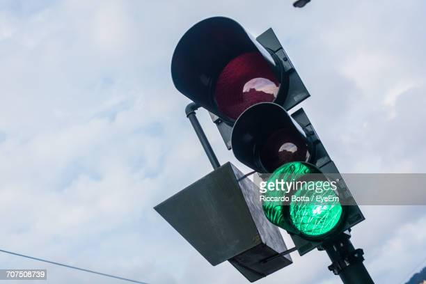 Low Angle View Of Stoplight Against Cloudy Sky