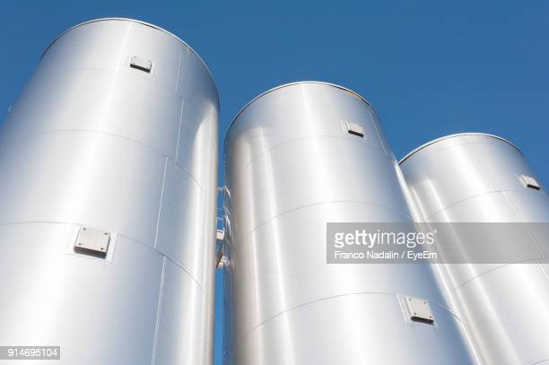 low angle view of storage tank against clear sky - silo stock photos and pictures