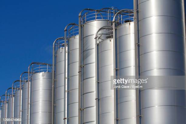 low angle view of storage tank in factory against sky - petrochemical plant stock pictures, royalty-free photos & images