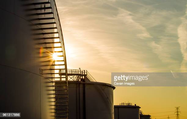 low angle view of storage tanks at oil refinery against sky during sunset - oil refinery stock pictures, royalty-free photos & images