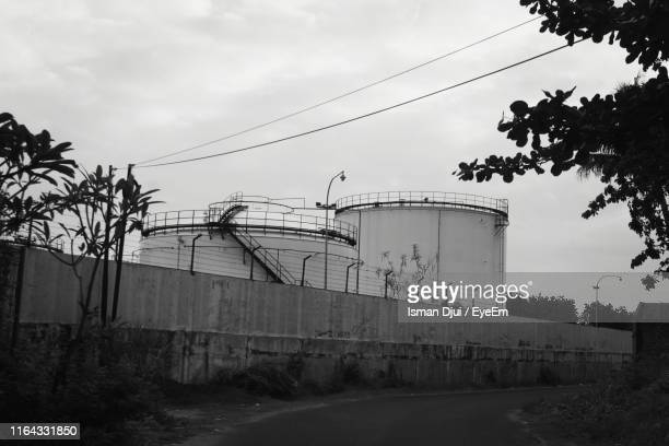 Low Angle View Of Storage Tanks By Fence Against Sky
