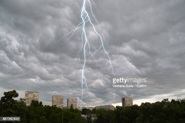 Low Angle View Of Storm Clouds And Lightning Over City