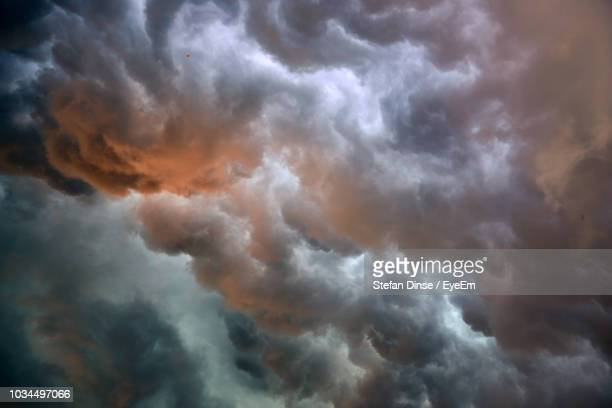 low angle view of storm clouds in sky - moody sky stock pictures, royalty-free photos & images