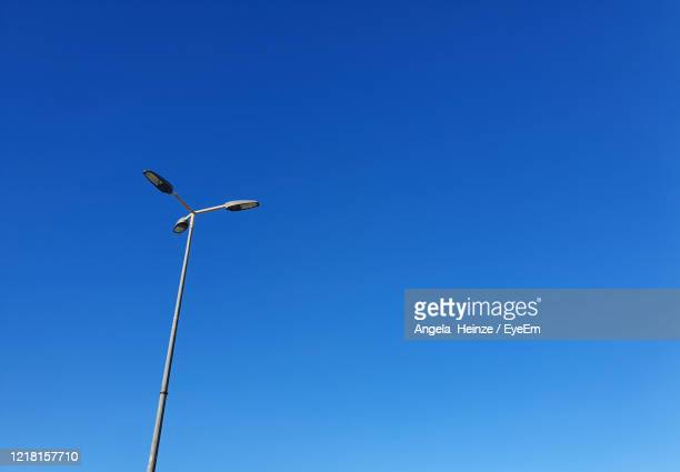low angle view of street light against clear blue sky - manacor stock pictures, royalty-free photos & images