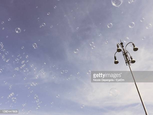 low angle view of street light against sky and soap balls - soapstone stock pictures, royalty-free photos & images