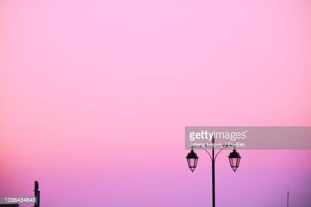 low angle view of street light against sky during sunset - jelena ivkovic stock pictures, royalty-free photos & images