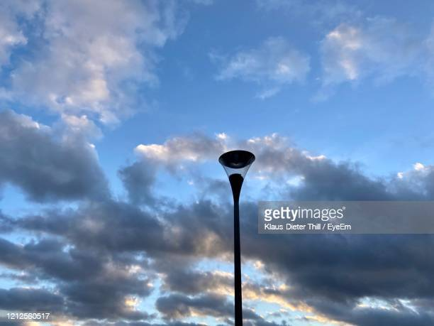 low angle view of street light against sky - klaus-dieter thill stock-fotos und bilder