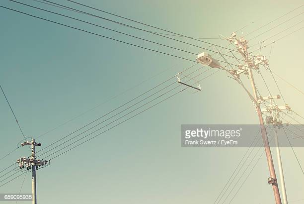 low angle view of street light and power line against sky - frank swertz stockfoto's en -beelden