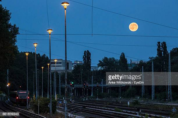 Low Angle View Of Street Light By Railroad Tracks Against Moon At Dusk