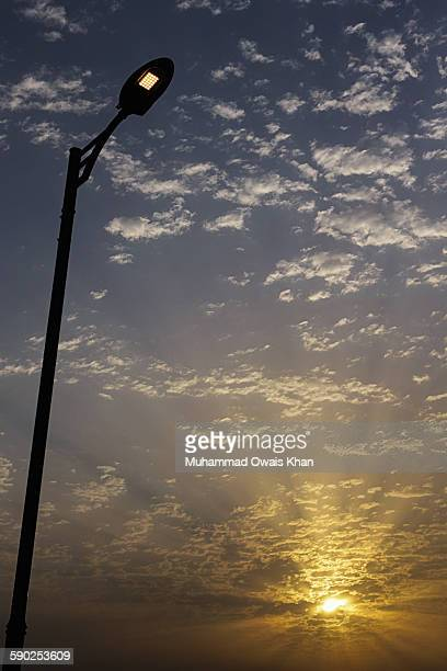 Low Angle View Of Street Light Poll Against Cloudy